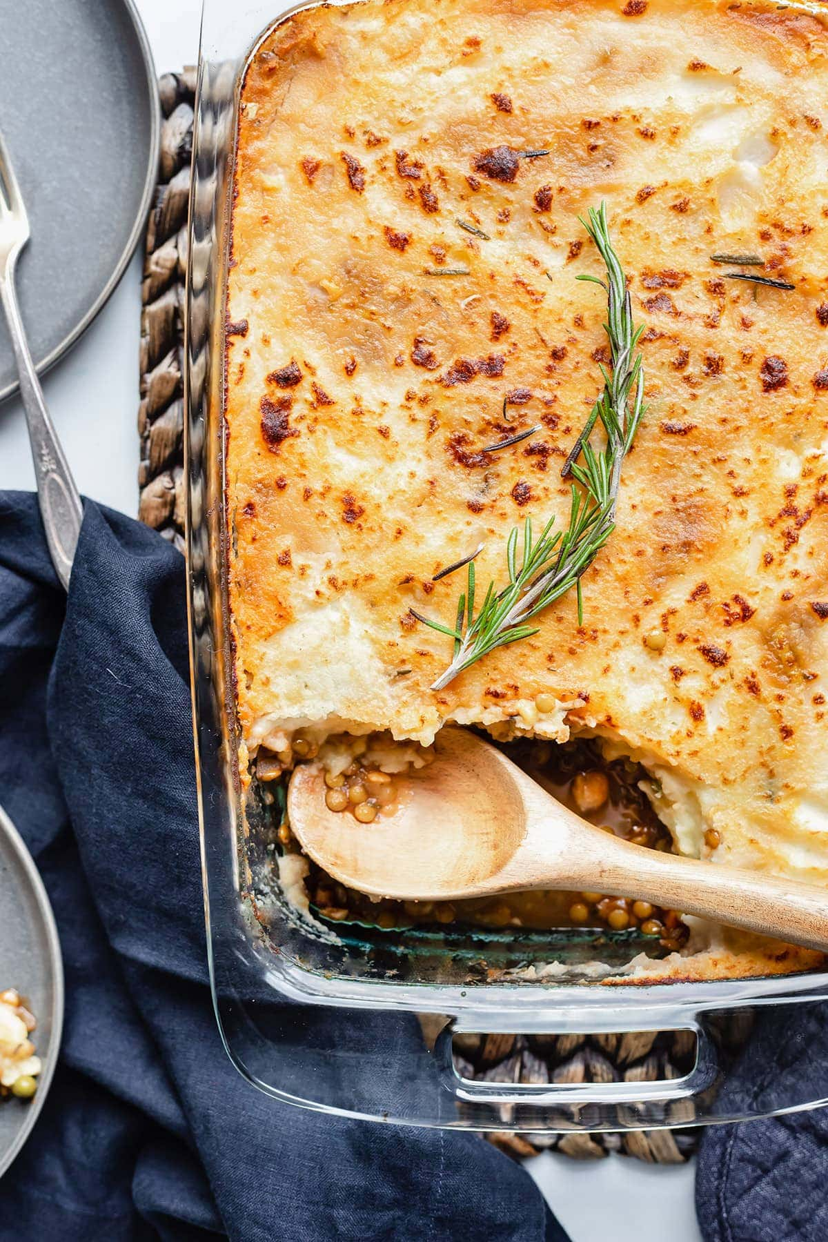 Overlay vegan lentil shepherd's pie in a rectangular glass dish on a brown background with a wooden spoon and rosemary sprig for garnish