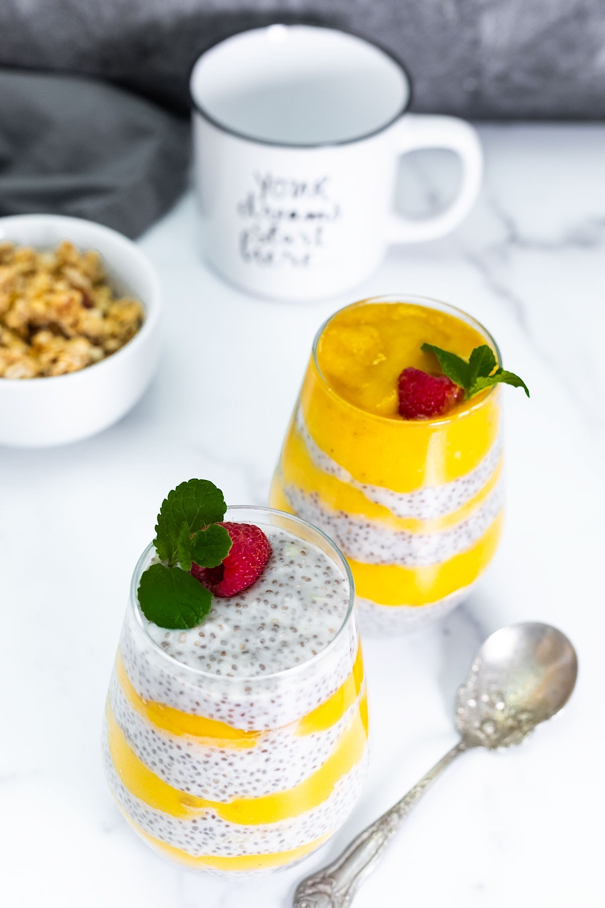overlay, mango chia pudding into 2 glass jars on a white background