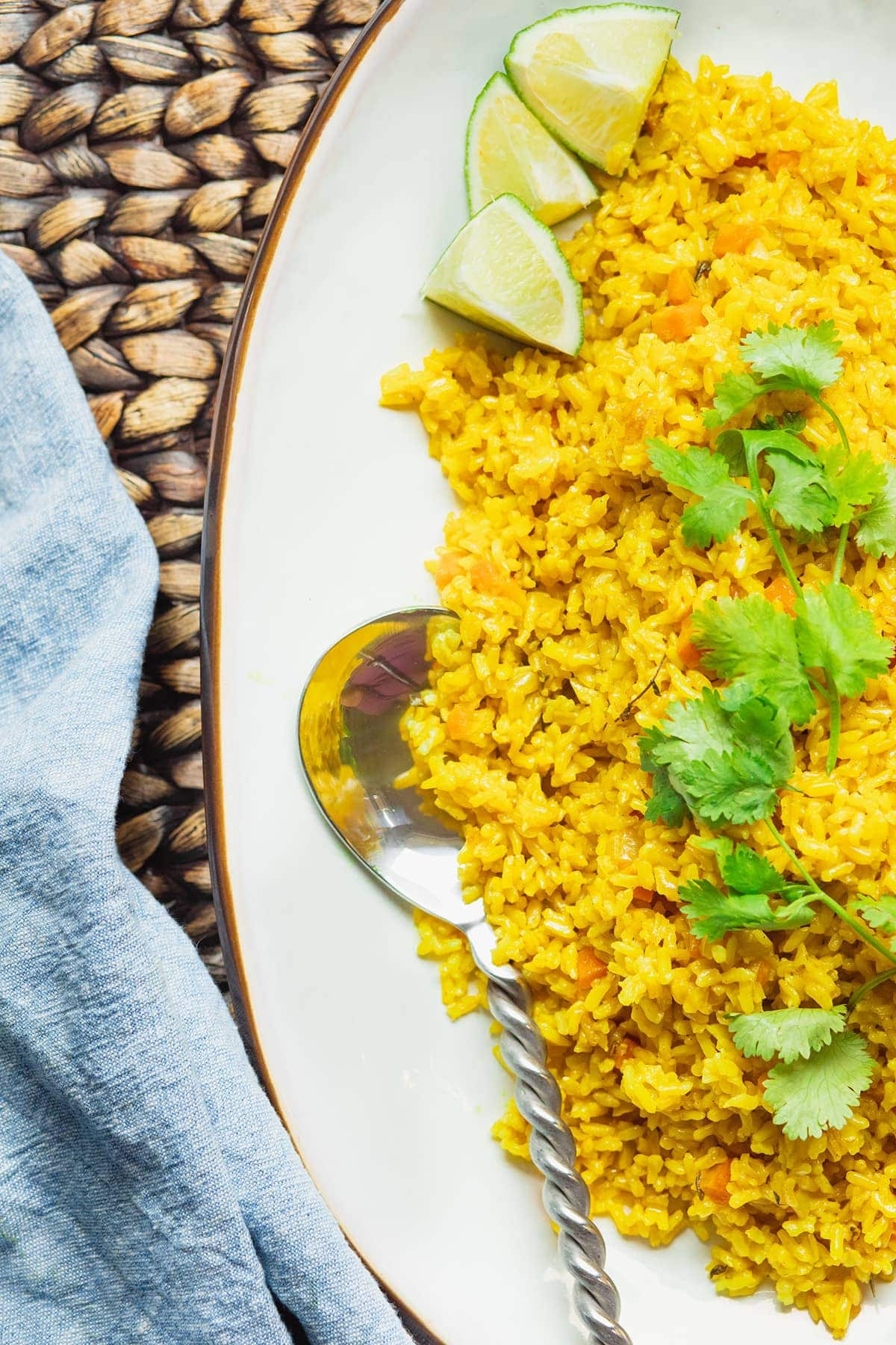 Close up of turmeric coconut rice on a white plate, golden spoon garnished with cilantro