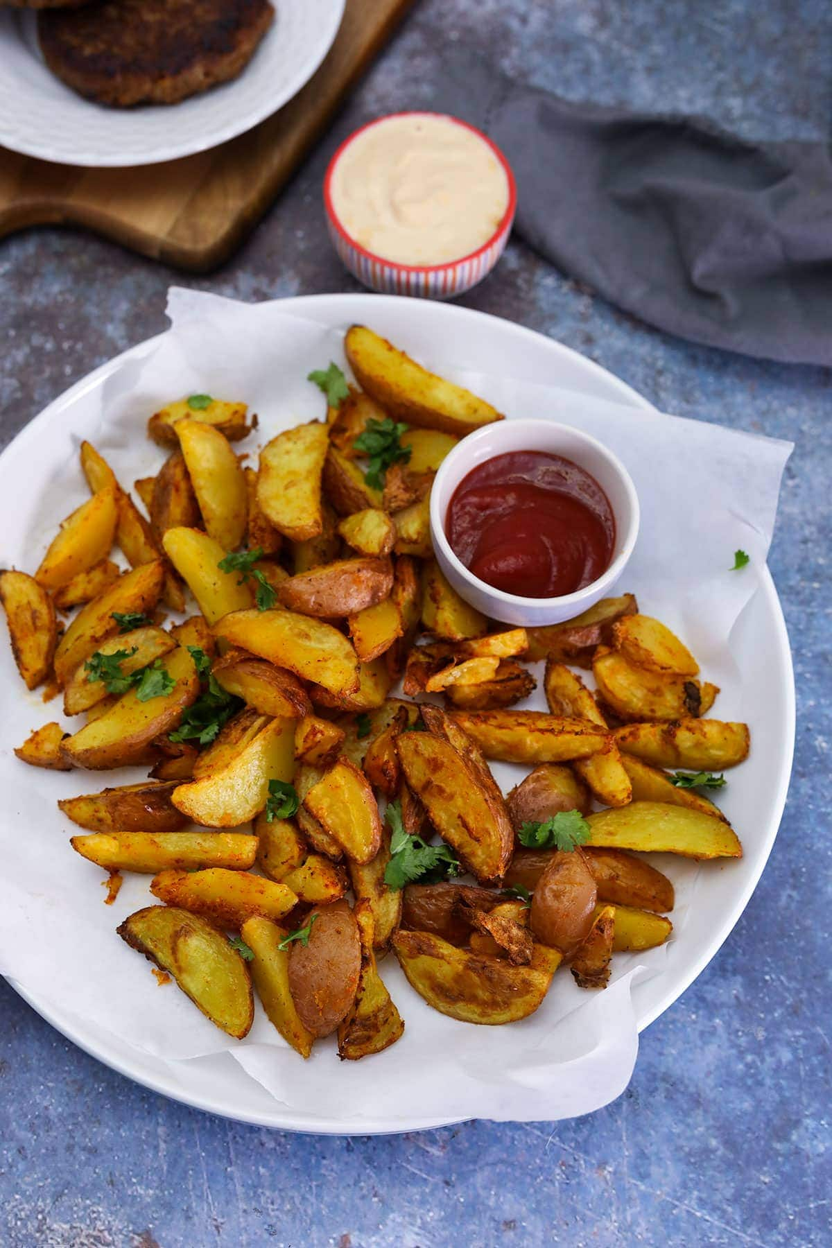 healthy air fryer fries on a white plate with ketchup and parsley for garnish