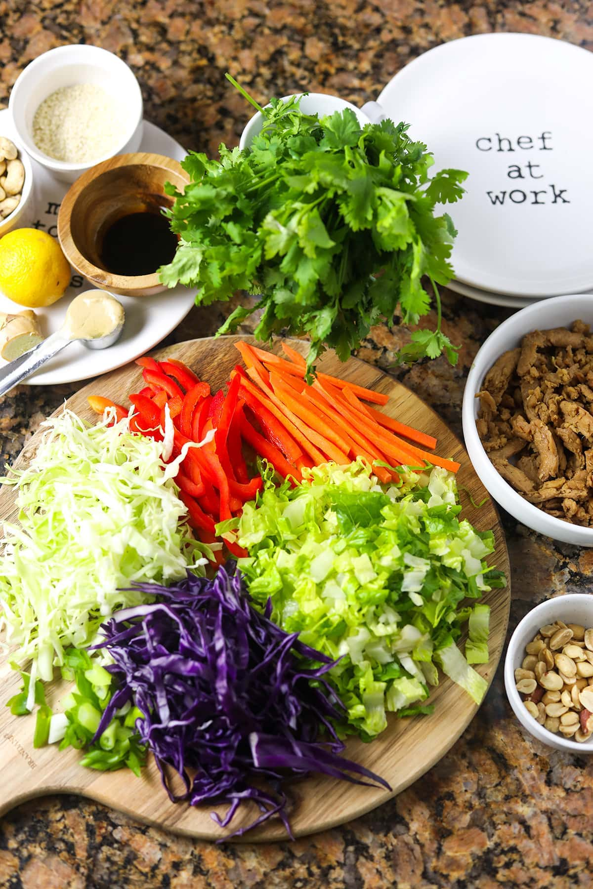 Overlay of asian salad ingredients, cabbages thinly sliced, romaine lettuce, marinade, on cutting board