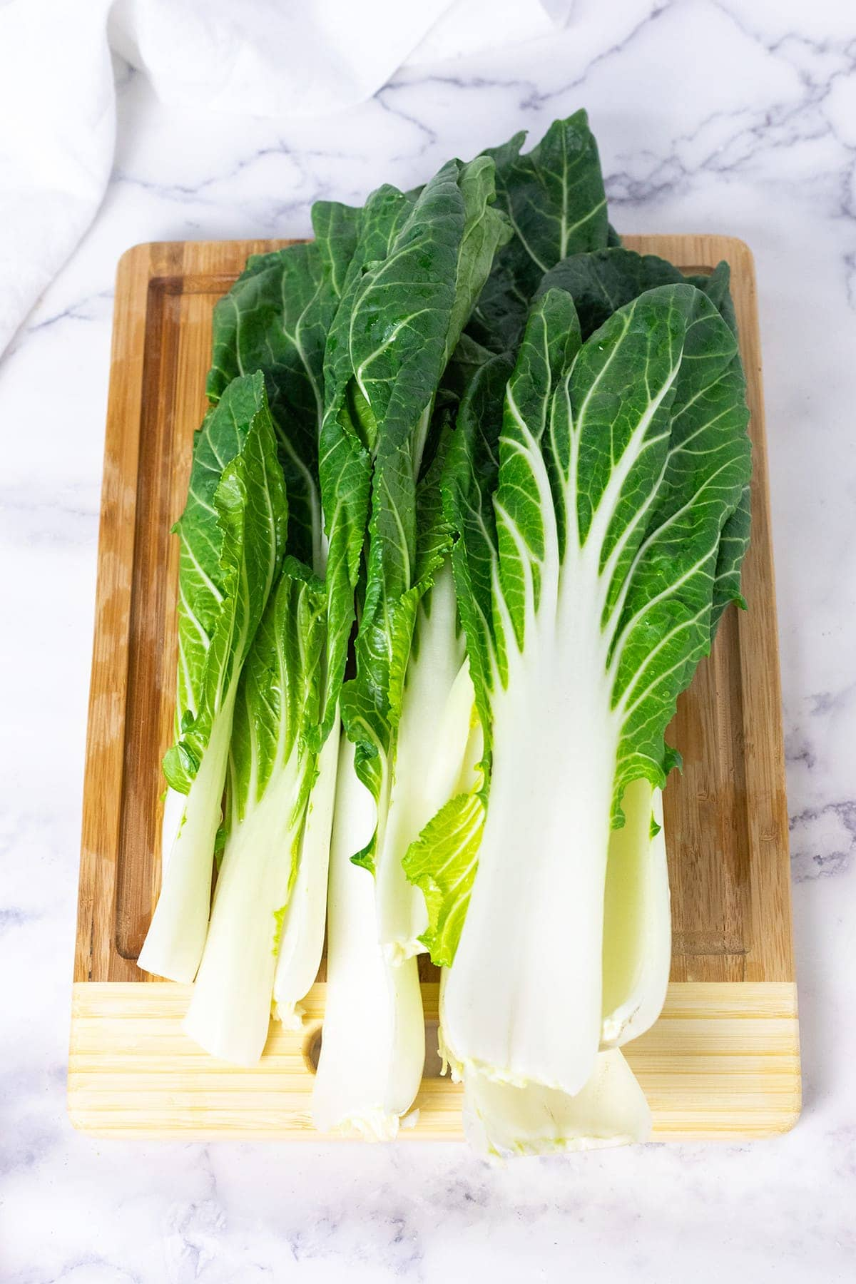 Bok choy base cut and stalks removed before washing on a cutting board on a white background