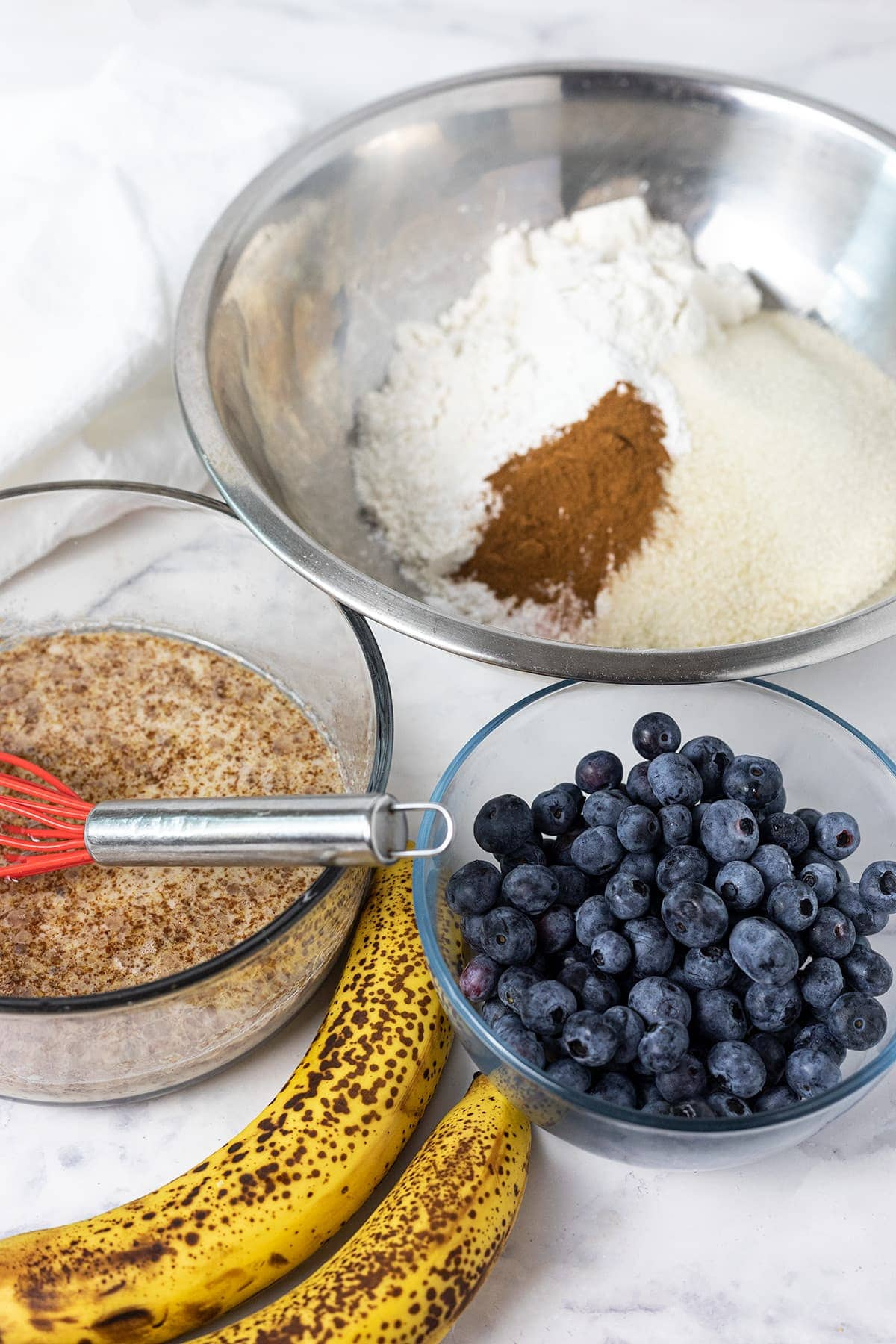 Ingredients for banana blueberry bread on a white background with a whisk