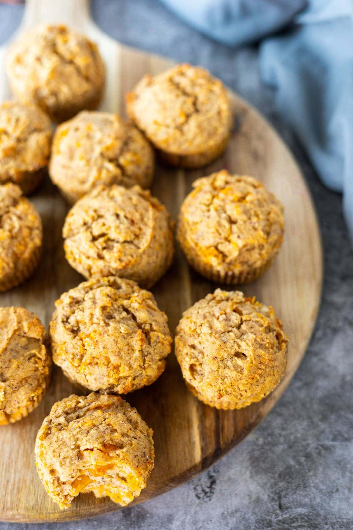 Overlay Gluten-free vegan butternut quash muffins on a round cutting board on a grey concrete with a grey apron