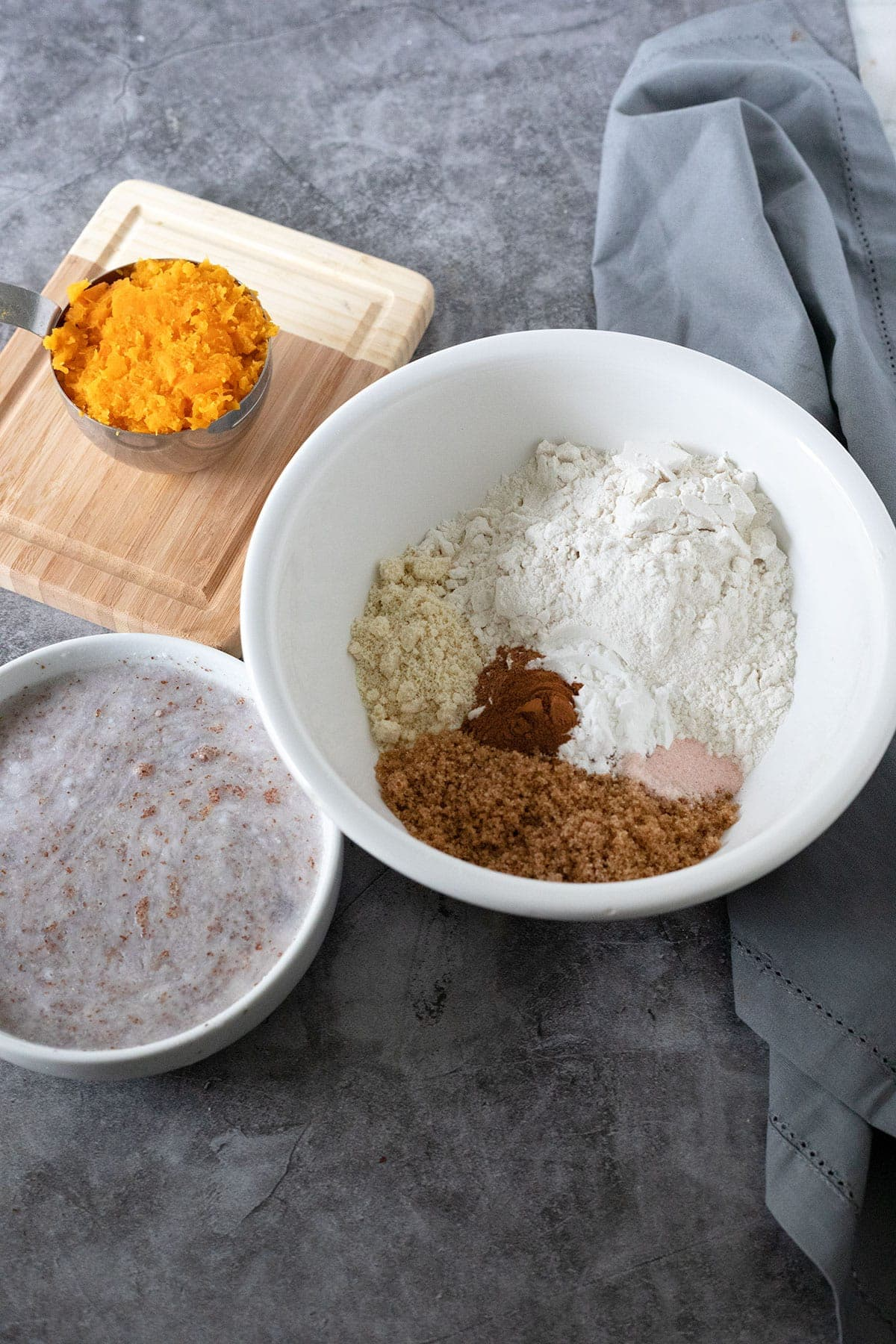 ingredients of butternut squash muffins in dry ingredients in white bowl, liquid ingredients in white and mashed butternut squash in measuring cup