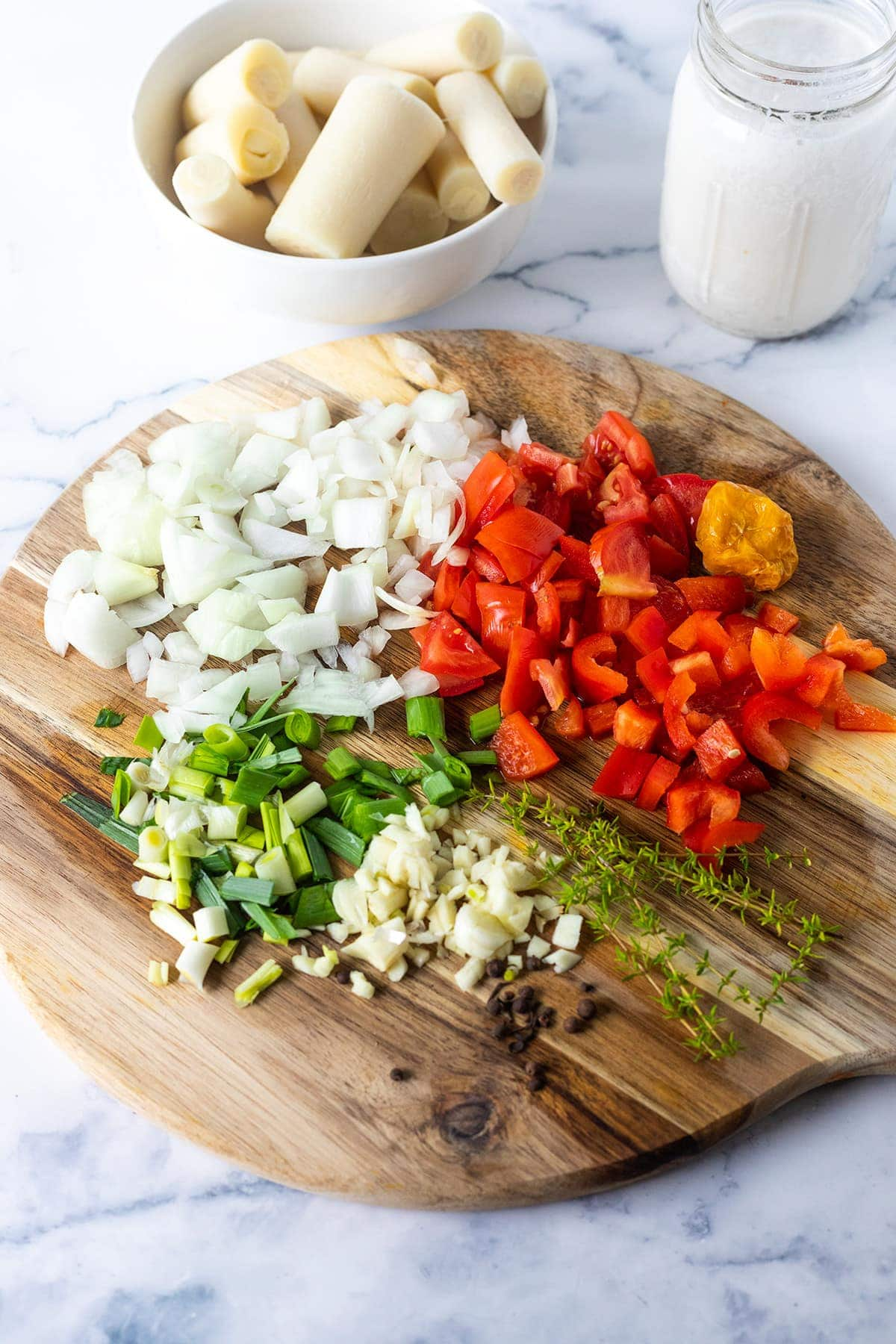 vegan salt fish rundown ingredients on cutting board with hearts of palm in white bowl
