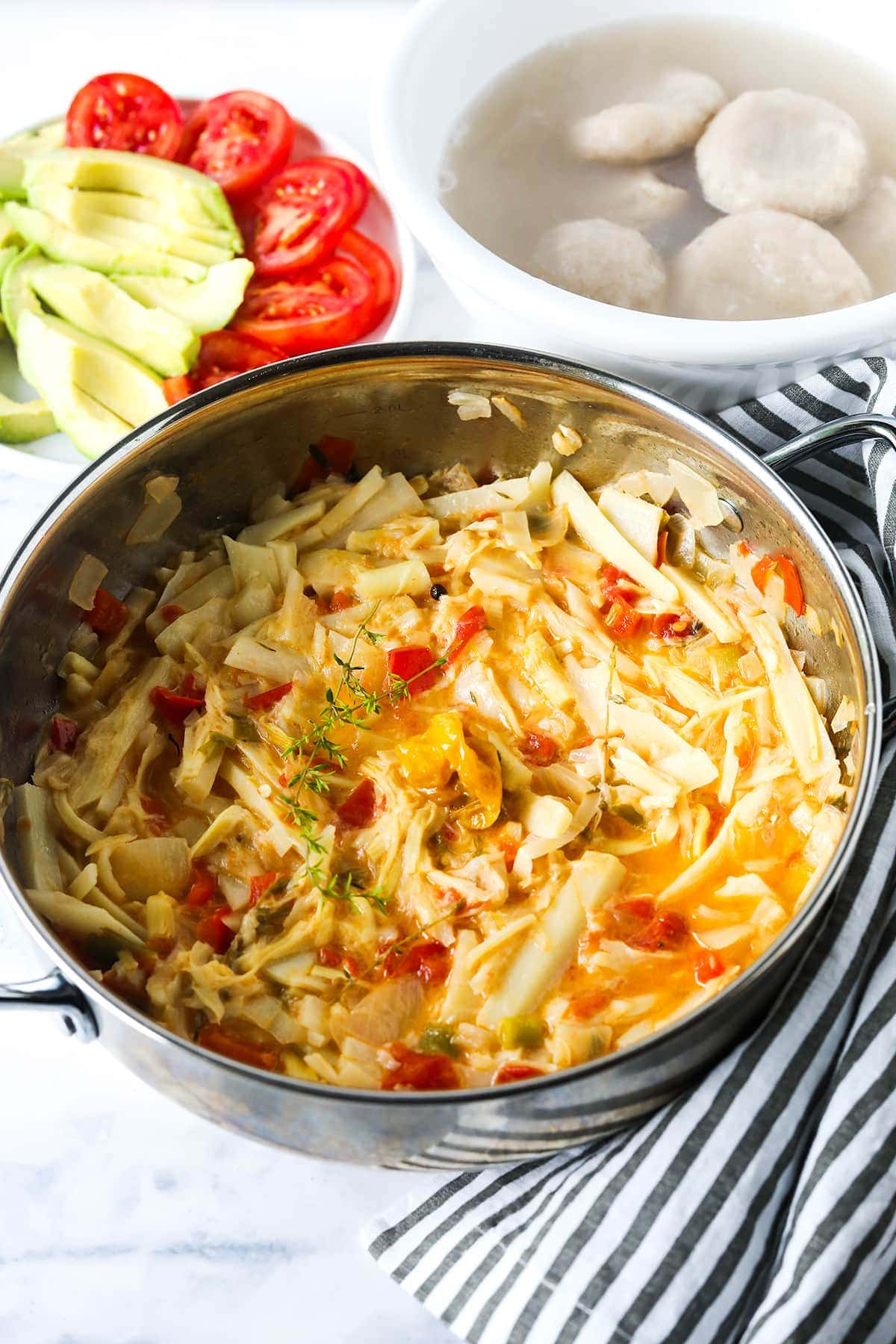 overlay vegan saltfish in a saucepan with dumplings in a white bowl, avocado and tomato slices on a white plate on a white background