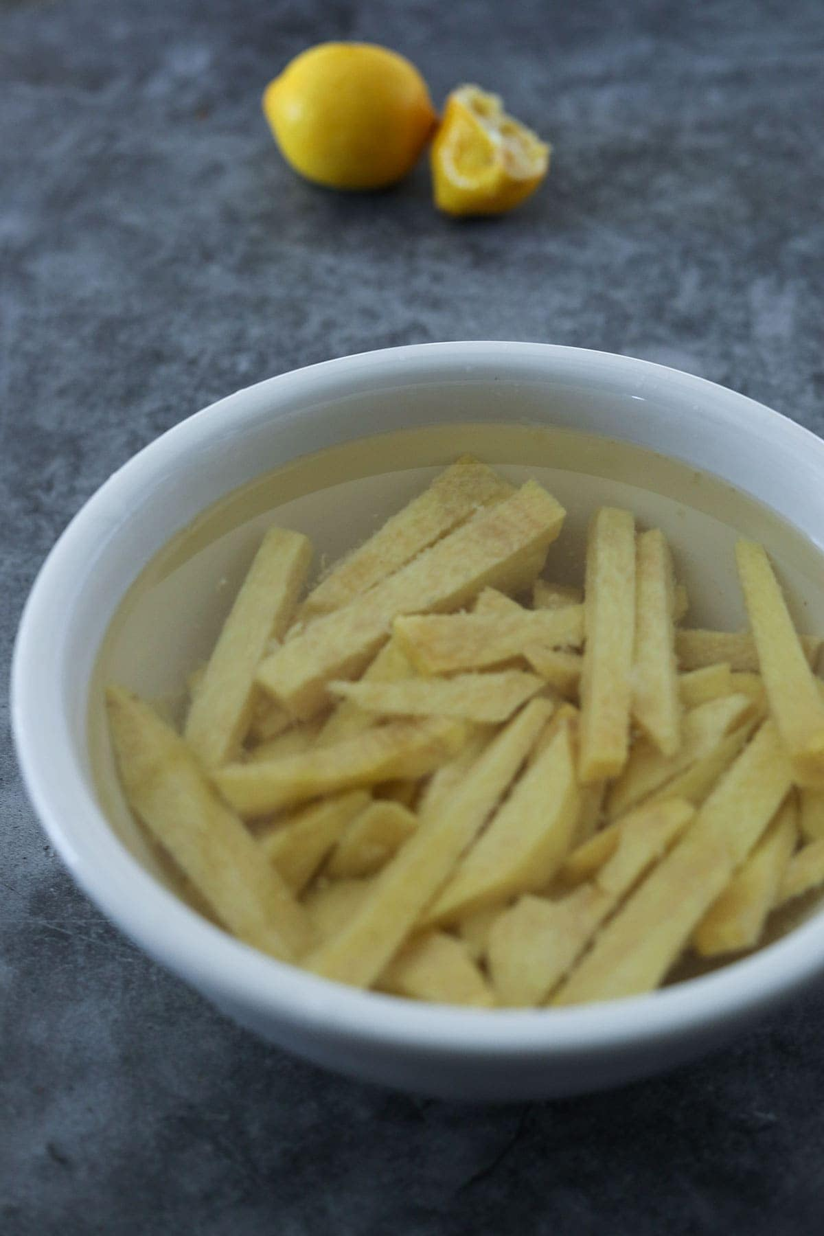 yam cut into match sticks for fries, soaking in lemon water