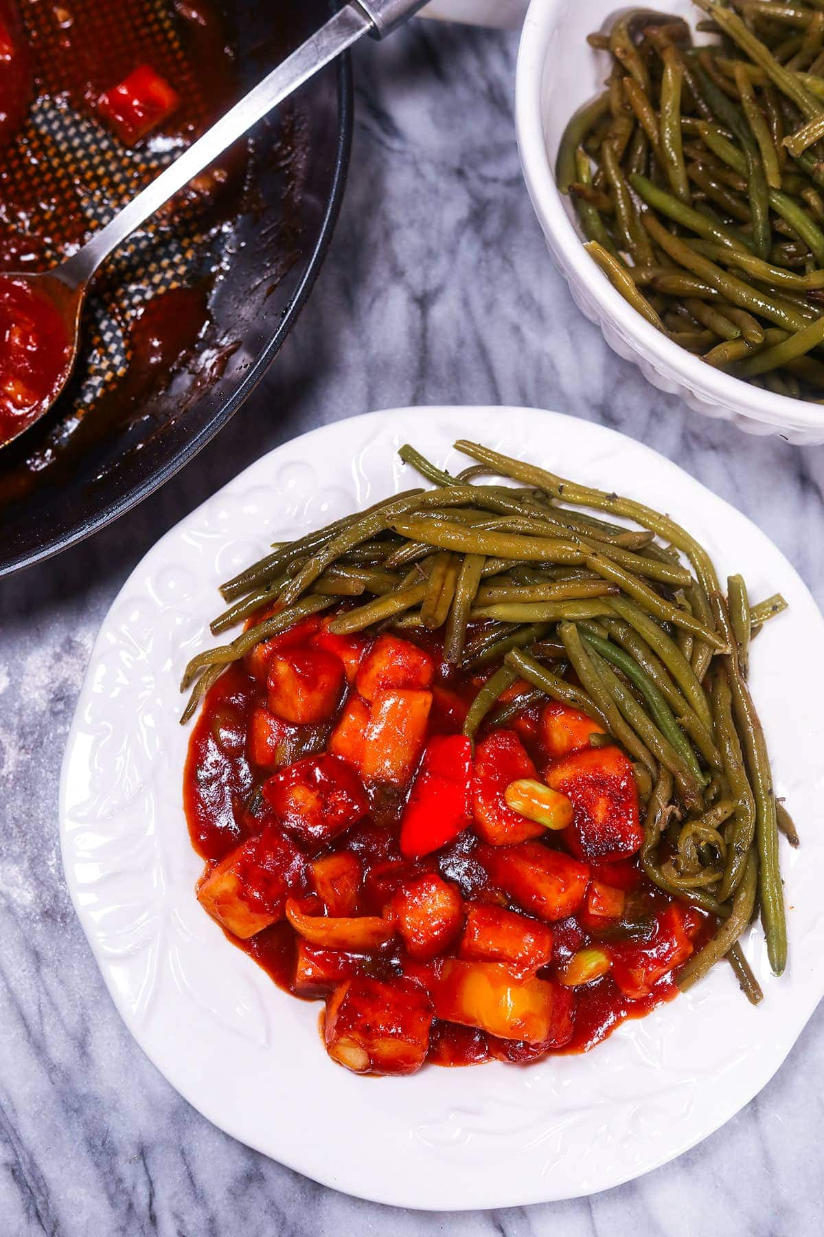 sweet and sour tofu on a white plate with green beans and a white bowl of green beans in the back