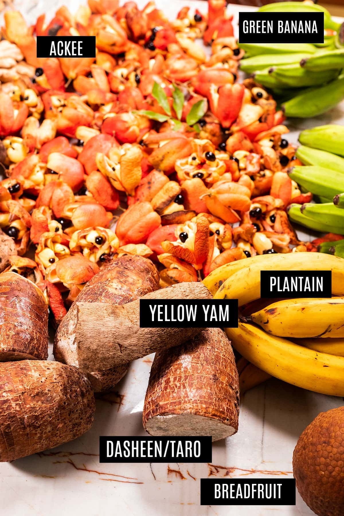 yellow yam with Jamaican produce, ackee, plantain, green banana, dasheen on a marbled counter