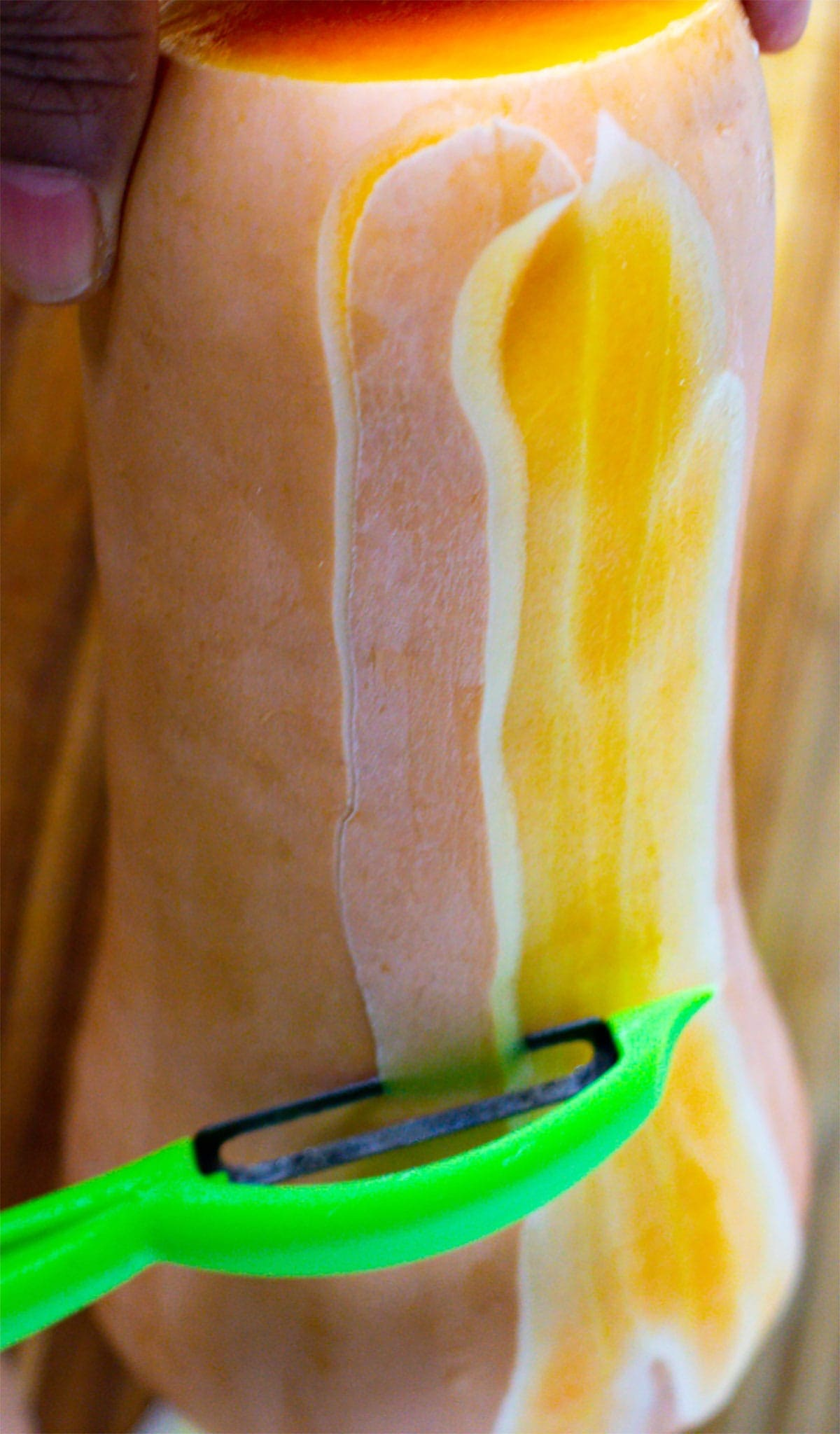 Peeling butternut squash with a vegetable peeler