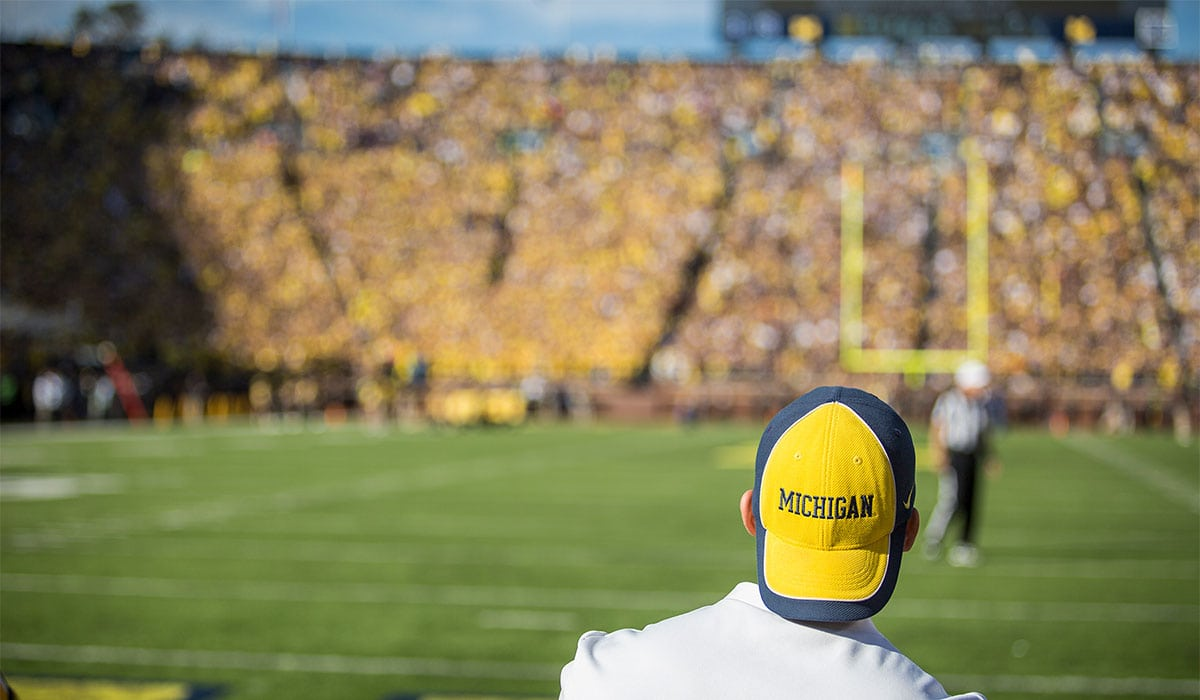Michigan football fan looks on from crowd during game at Michigan Stadium