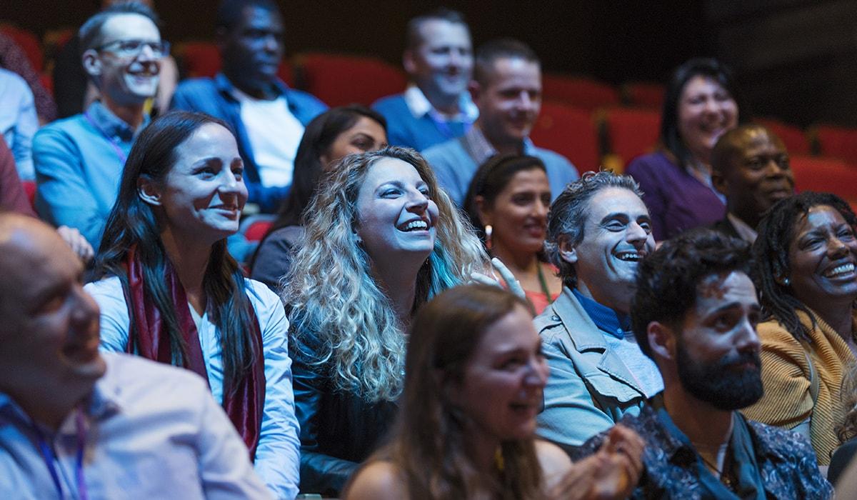 Smiling, Enthusiastic Audience In Dark Auditorium