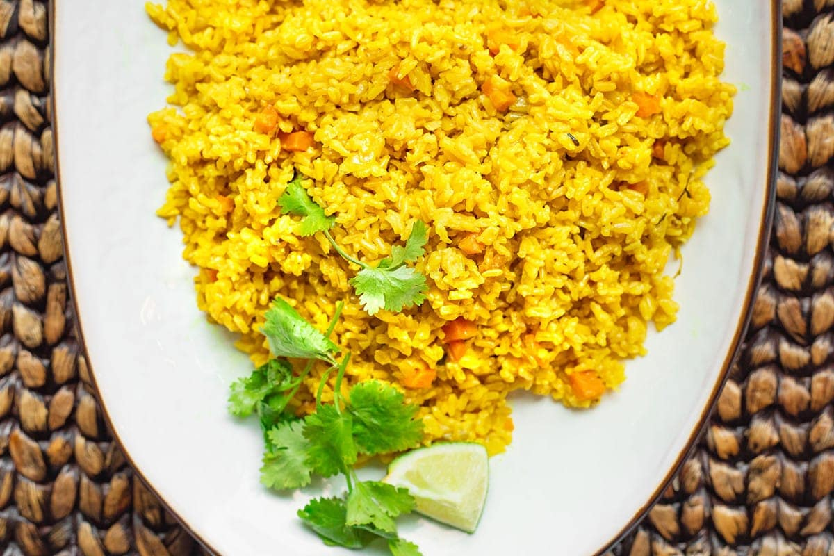 Overlay of yellow turmeric coconut rice garnished with cilantro on a white plateOverlay of yellow turmeric coconut rice garnished with cilantro on a white plate