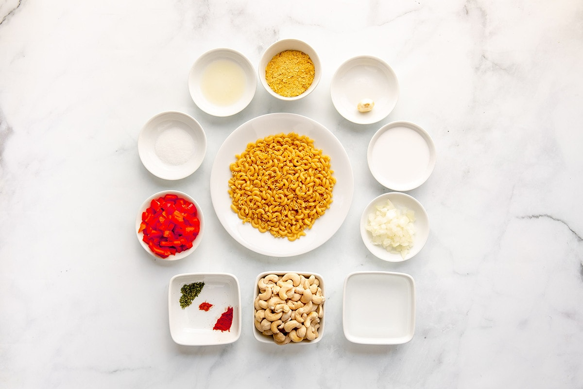 Overlay image of ingredients for vegan mac and cheese in with bowls macaroni, red bell pepper, cashew, yeast flakes