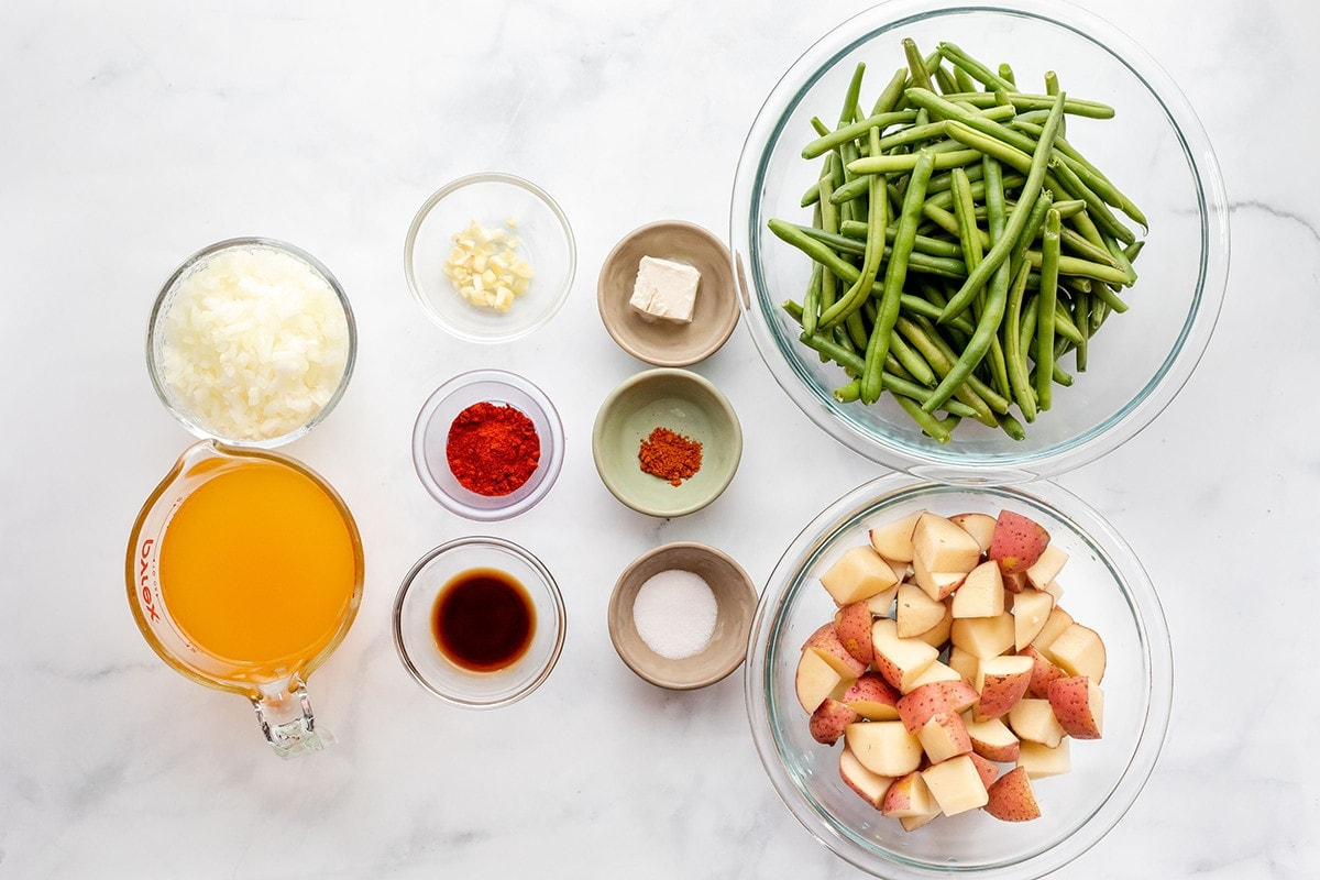 Ingredients for vegan southern green beans and potatoes on a white marble background