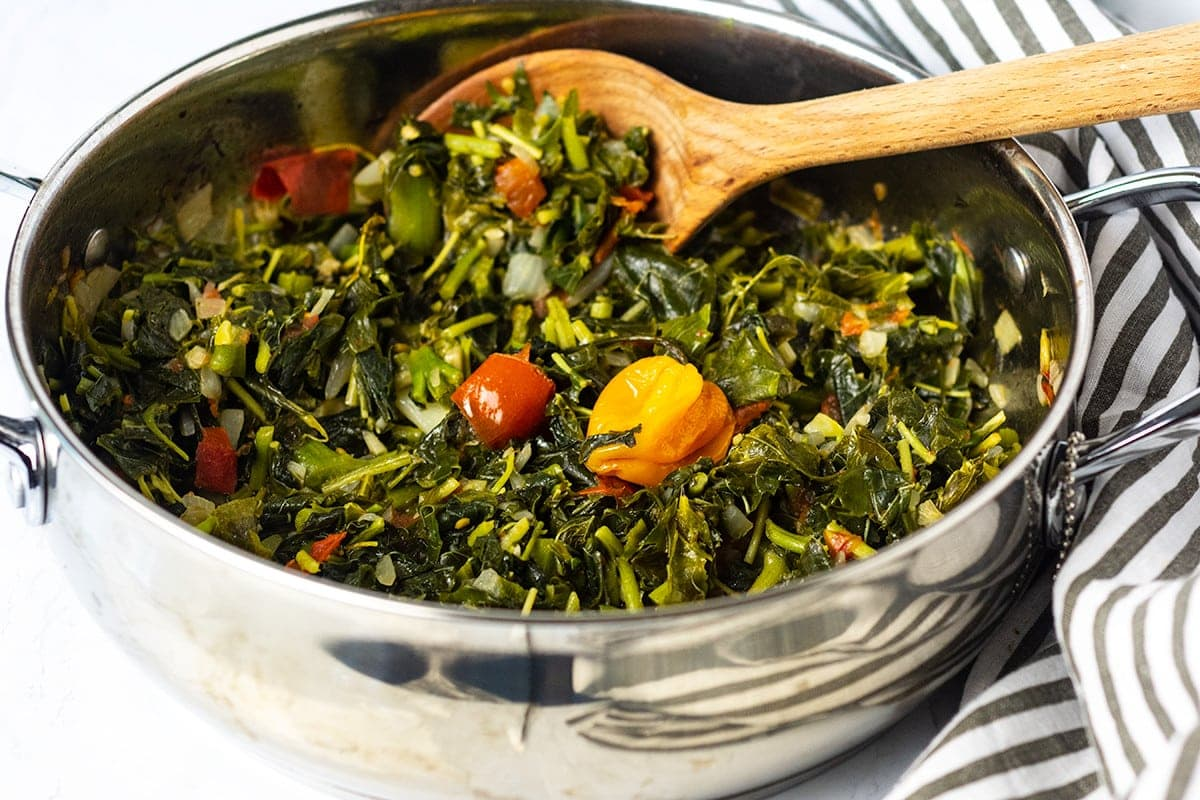 Jamaican cooked callaloo in a silver saucepan with a wooden spoon on a white background