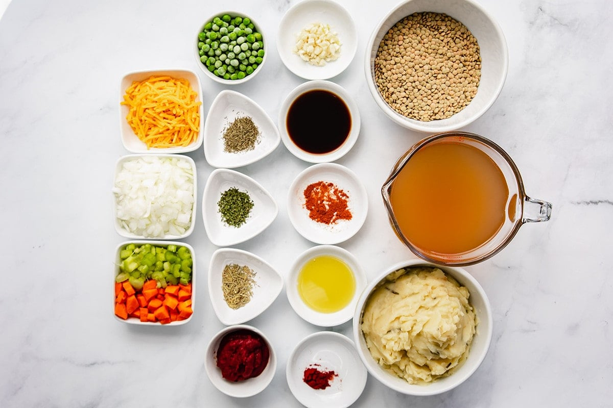 Ingredients for vegan lentil shepherd's pie on an overlay with a white background in small containers