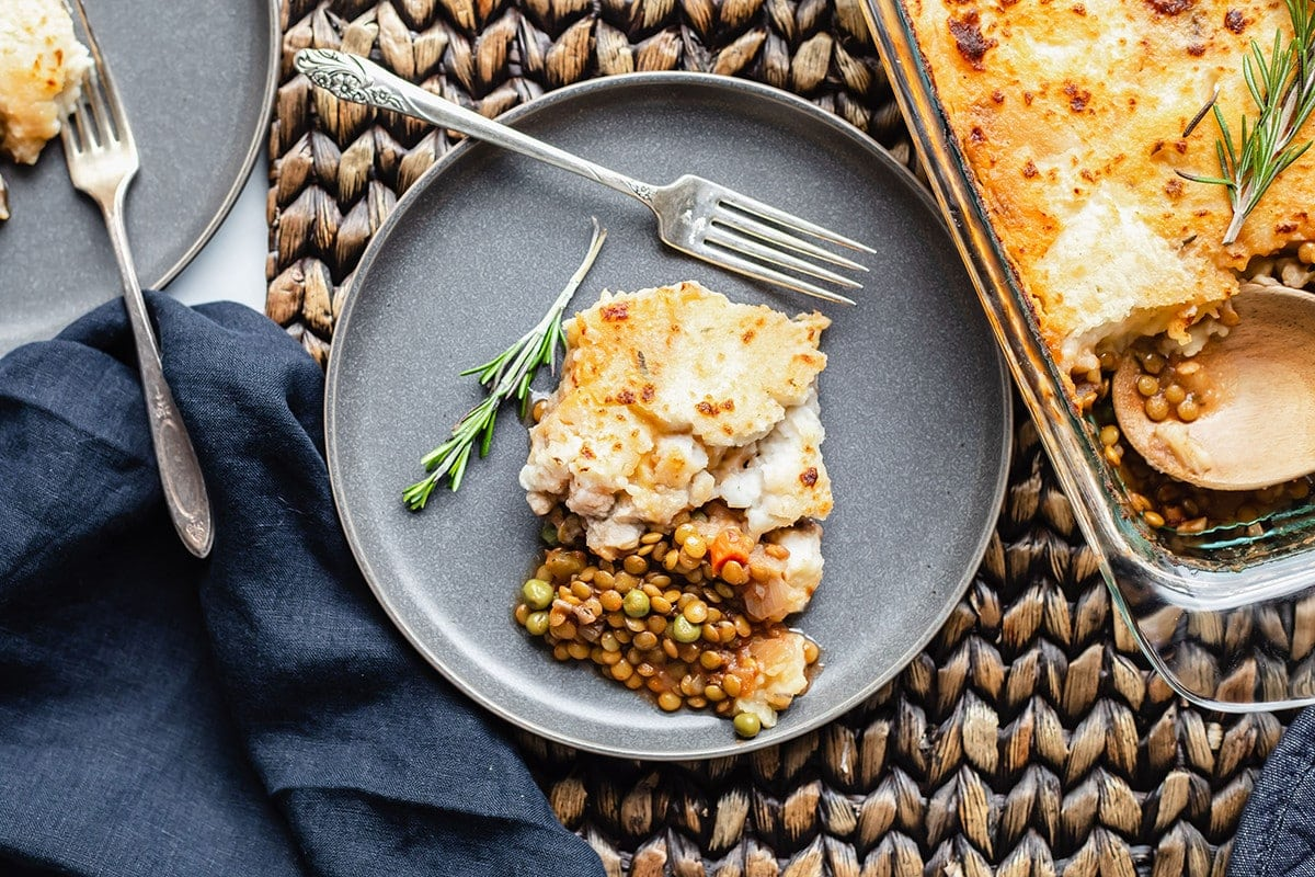 Overlay serving of lentil shepherd's pie on a grey plate with a fork and garnished with rosemary sprig with a blue napkin on a brown background