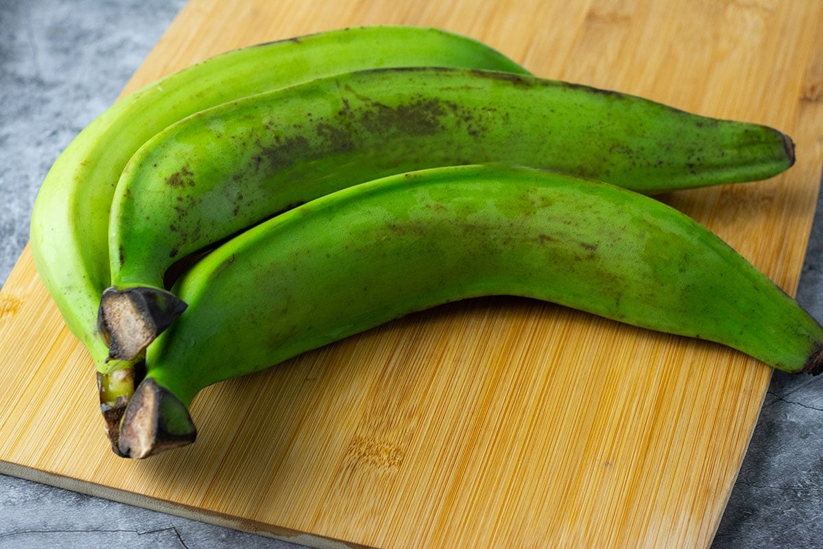 Green plantains on a cutting board for air fryer plantain chips