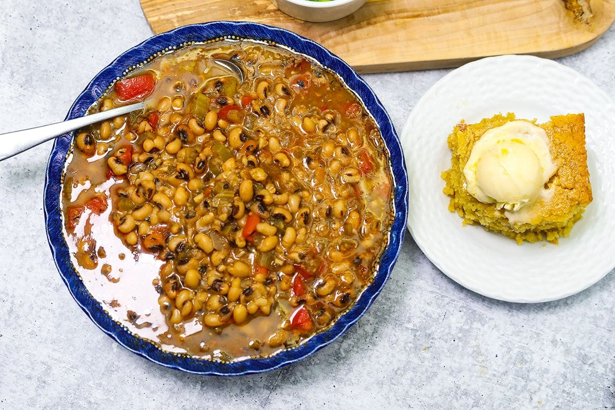 black eyed peas in a blue bowl next to a white plate with a slice of cornbread on white concrete background