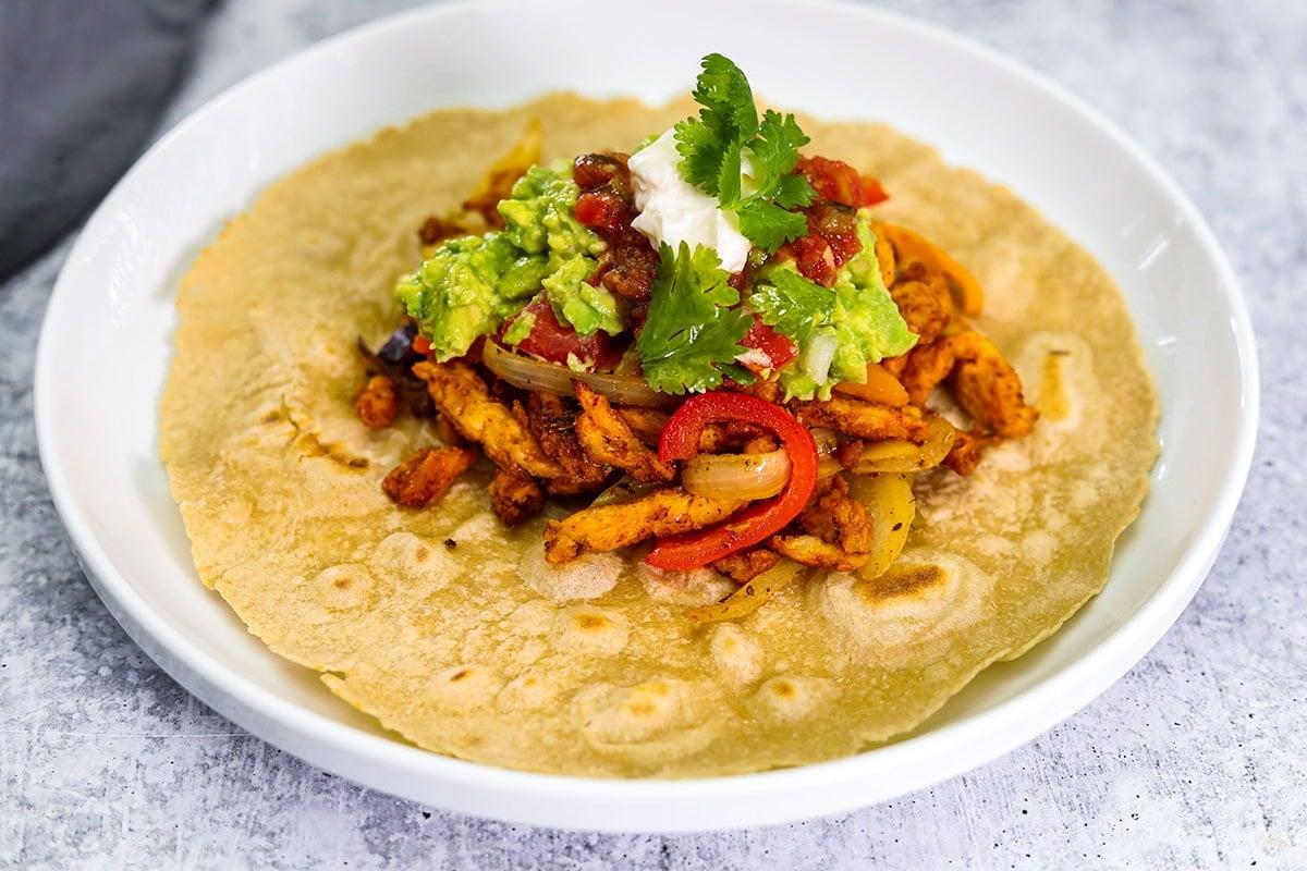 veggie fajita on tortilla topped with vegan sour cream, guacamole, salsa, cilantro