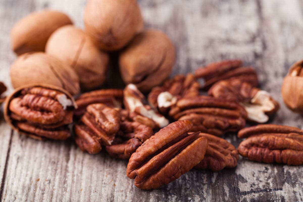 Whole and shelled pecans on a wooden background