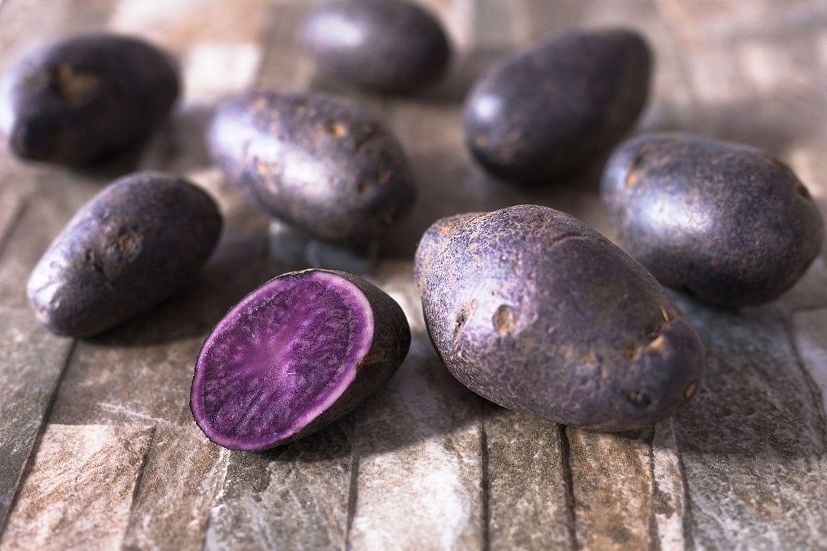 purple potatoes on wooden background