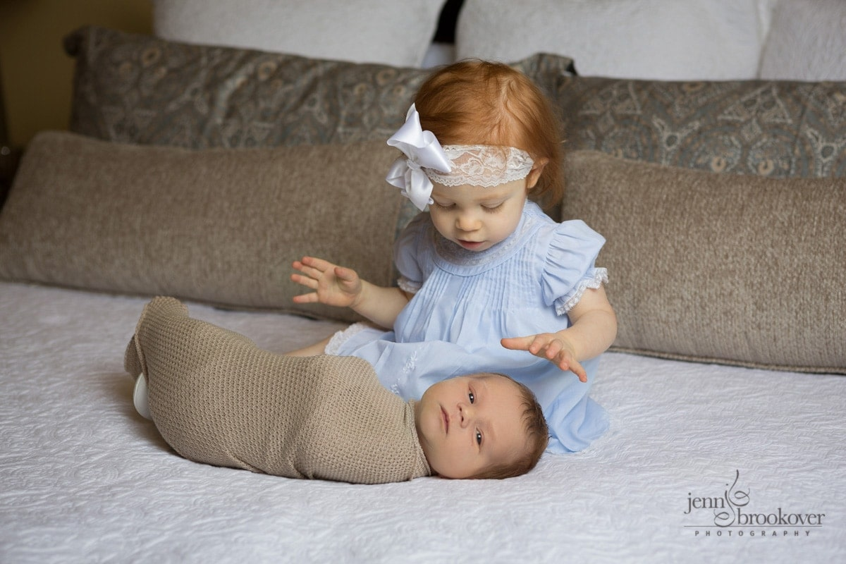 newborn with sister smiling and in awe of baby brother during photo session