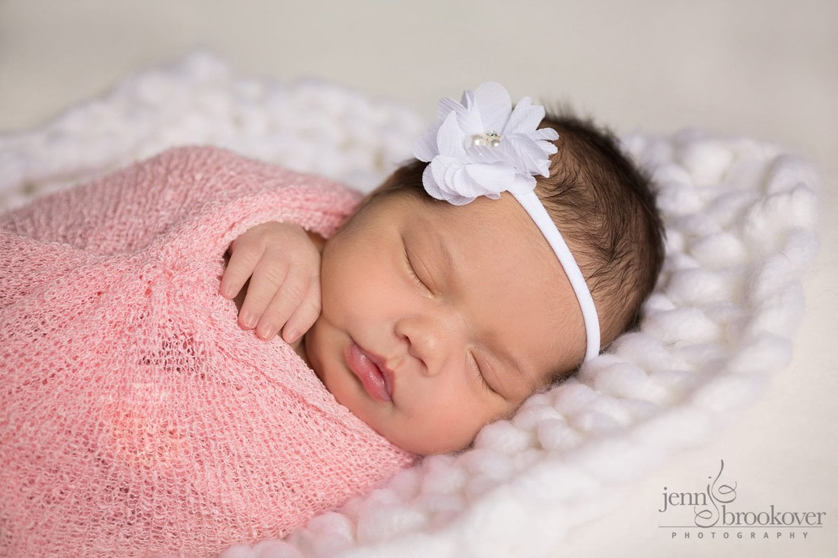 newborn wrapped in pink with white flower headband during her photo shoot with Jenn Brookover in San Antonio