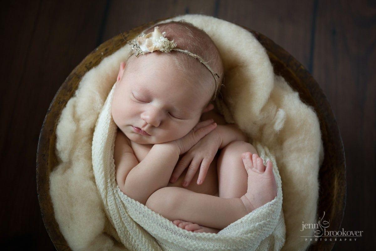 cuddled up newborn in cream wrap set in a bowl taken by Jenn Brookover in San Antonio