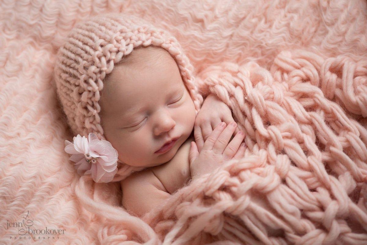 newborn baby girl in pink bonnet wth flower embellishment covered in knitted blanket taken by Jenn Brookover