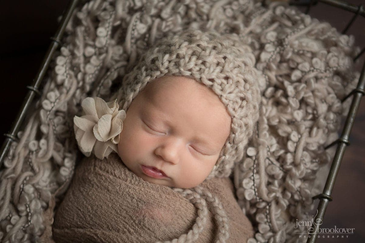 close up of newborn face wearing taupe knitted bonnet with flower asleep during her photo shoot with Jenn Brookover in San Antonio