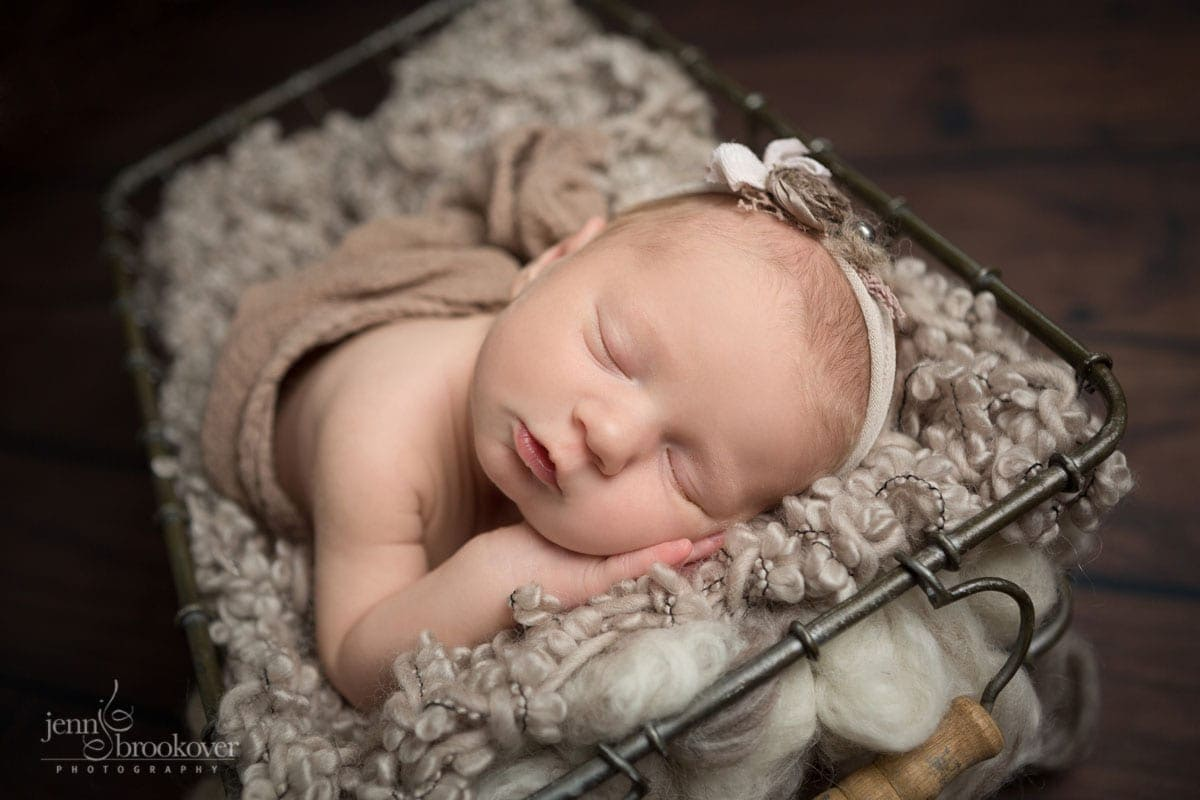 smiling newborn wrapped in taupe and sleeping for her newborn photo session at home with Jenn Brookover Photography in San Antonio
