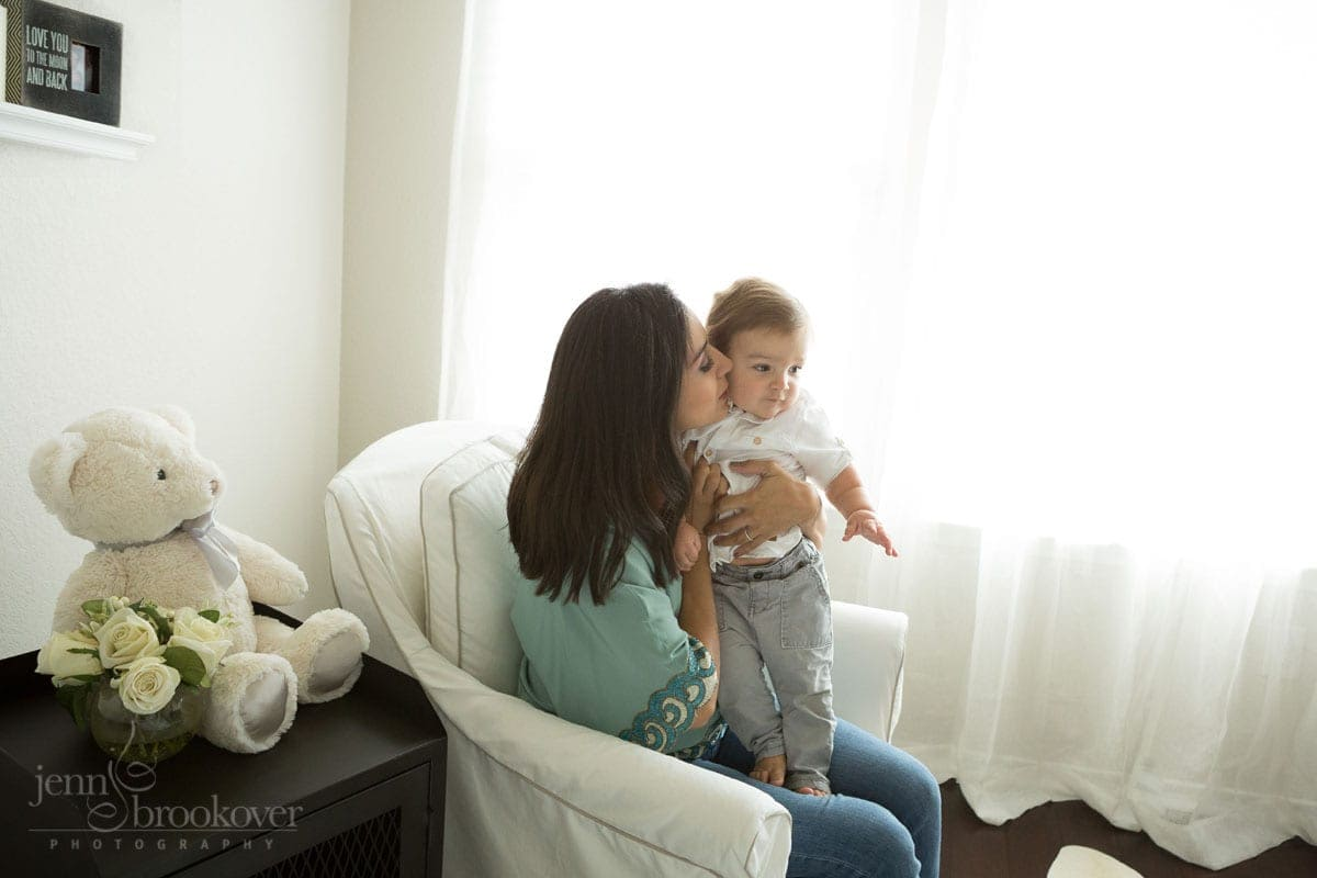mom kissing big brother during at home maternity session in San Antonio