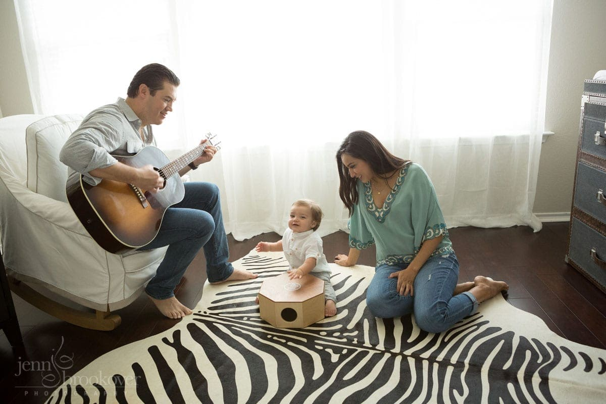 mom dad and toddler singing on a zebra rug in the nursery during maternity session in San Antonio, Texas