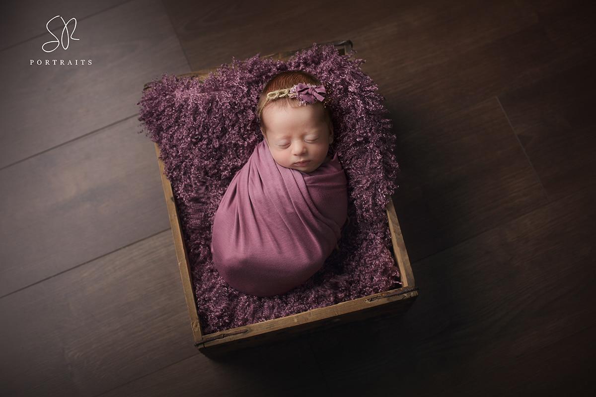 Newborn baby girl in purple wrap in basket prop. Photography Nottinghamshire