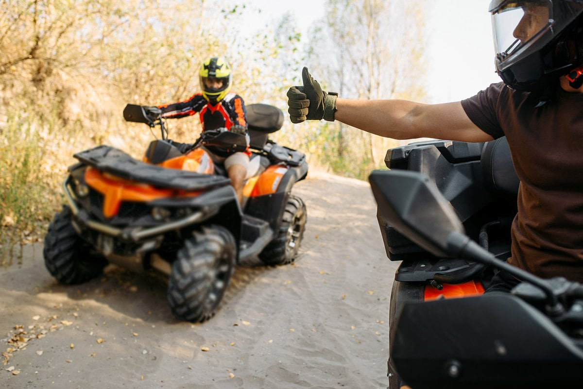 ATV rider in helmet showing thumbs up to his partner, offroad trip in the forest. Riding on quad bike, extreme sport and travelling, quadbike adventure