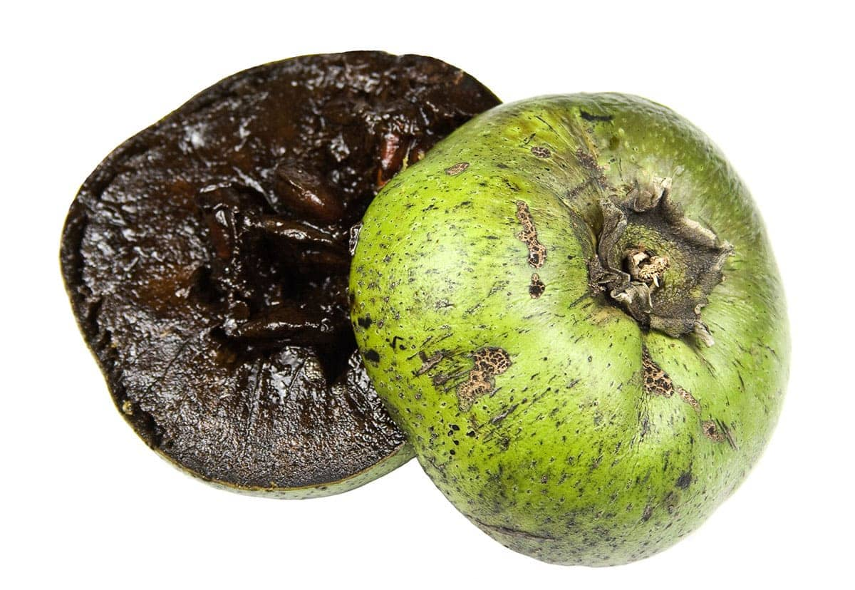 black sapote cut into half with green skin and black flesh on a white background