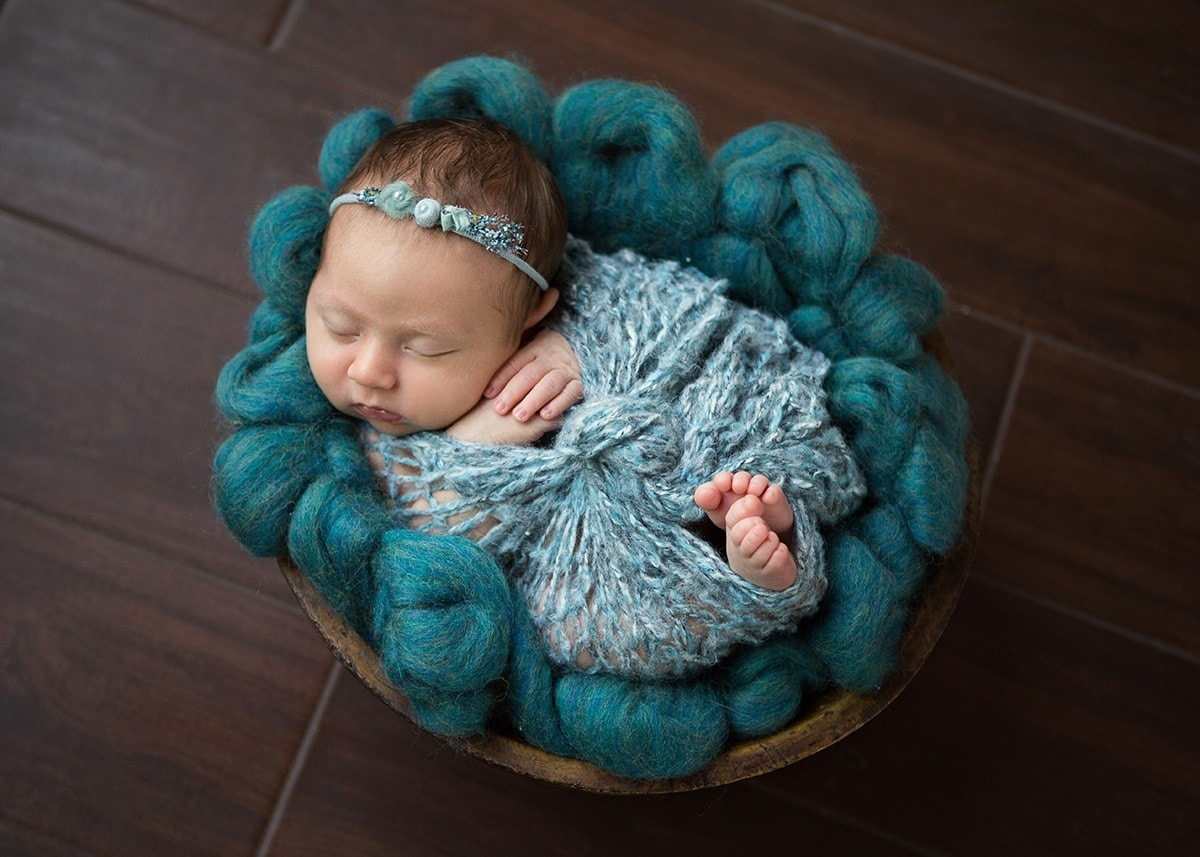 baby in bowl wrapped in teal captured by Jenn Brookover Newborn Photographer San Antonio