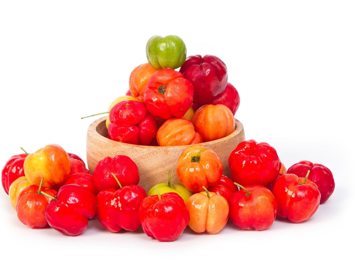 barbados cherries in a wooden bowl on a white background
