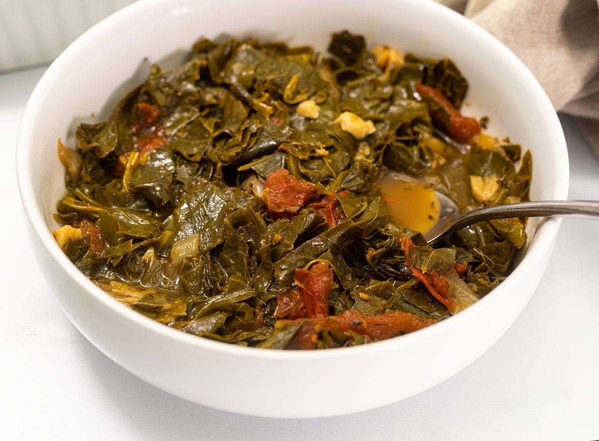 cooked collard greens in a white bowl with a spoonful of likker