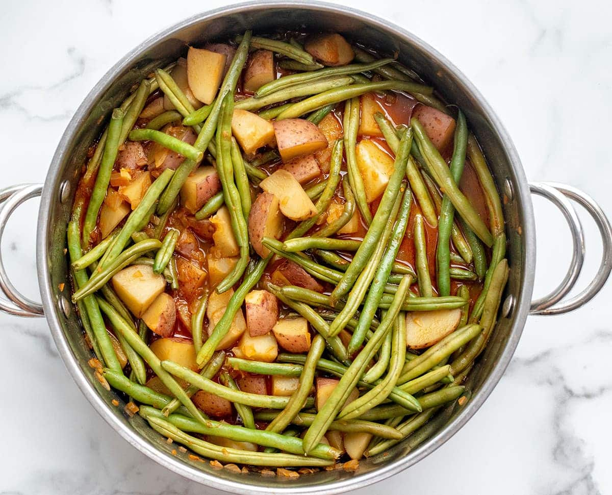 vegan southern green beans and potatoes overlay in a saucepan on a white background