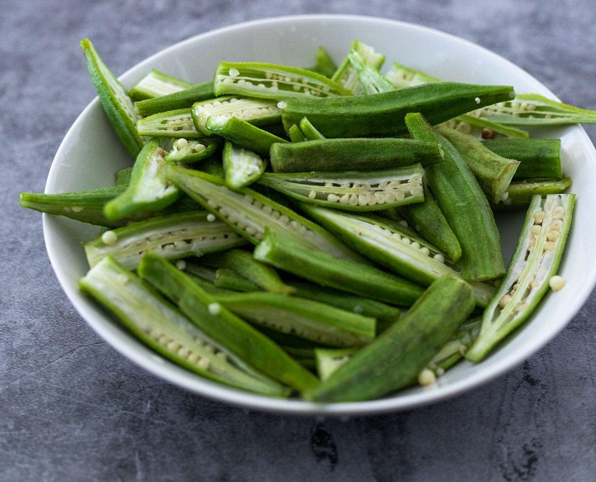 Okra cut in half lengthwise in a white bowl