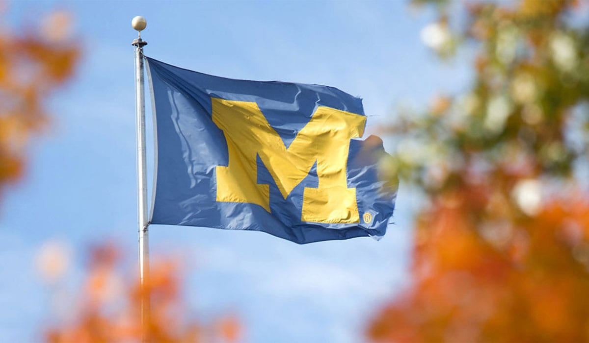 University of Michigan flag framed by orange and green leaves