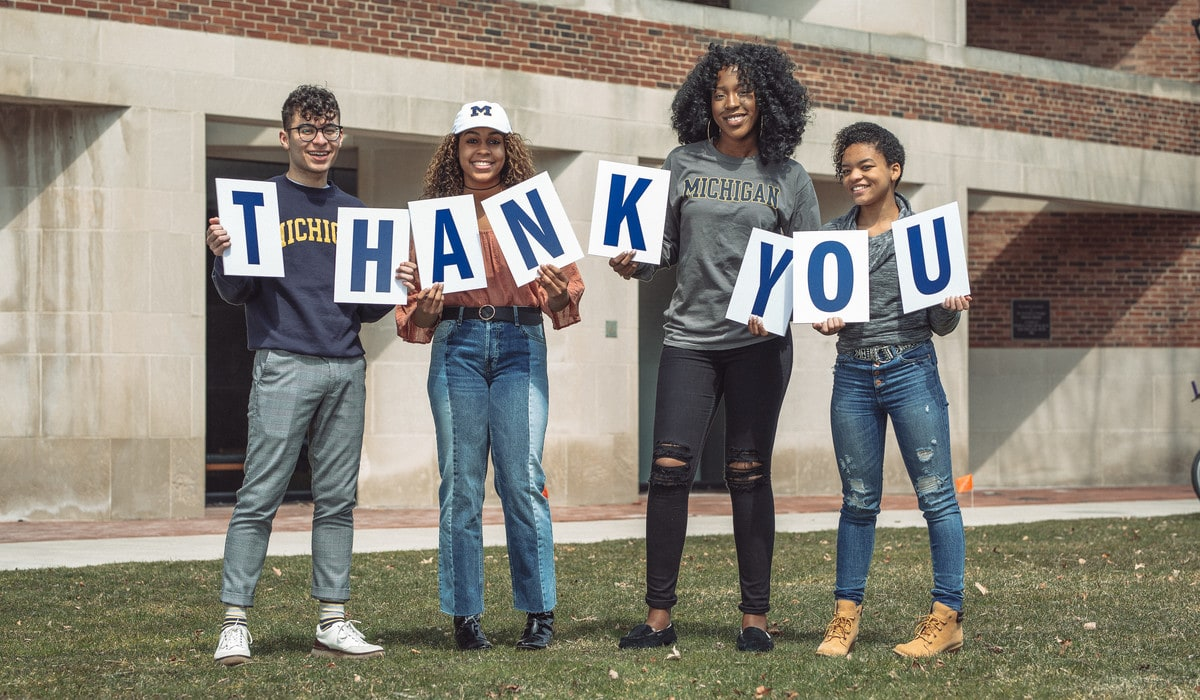"""LEAD Scholars hold a """"Thank You"""" sign outside the Alumni Center at the University of Michigan"""