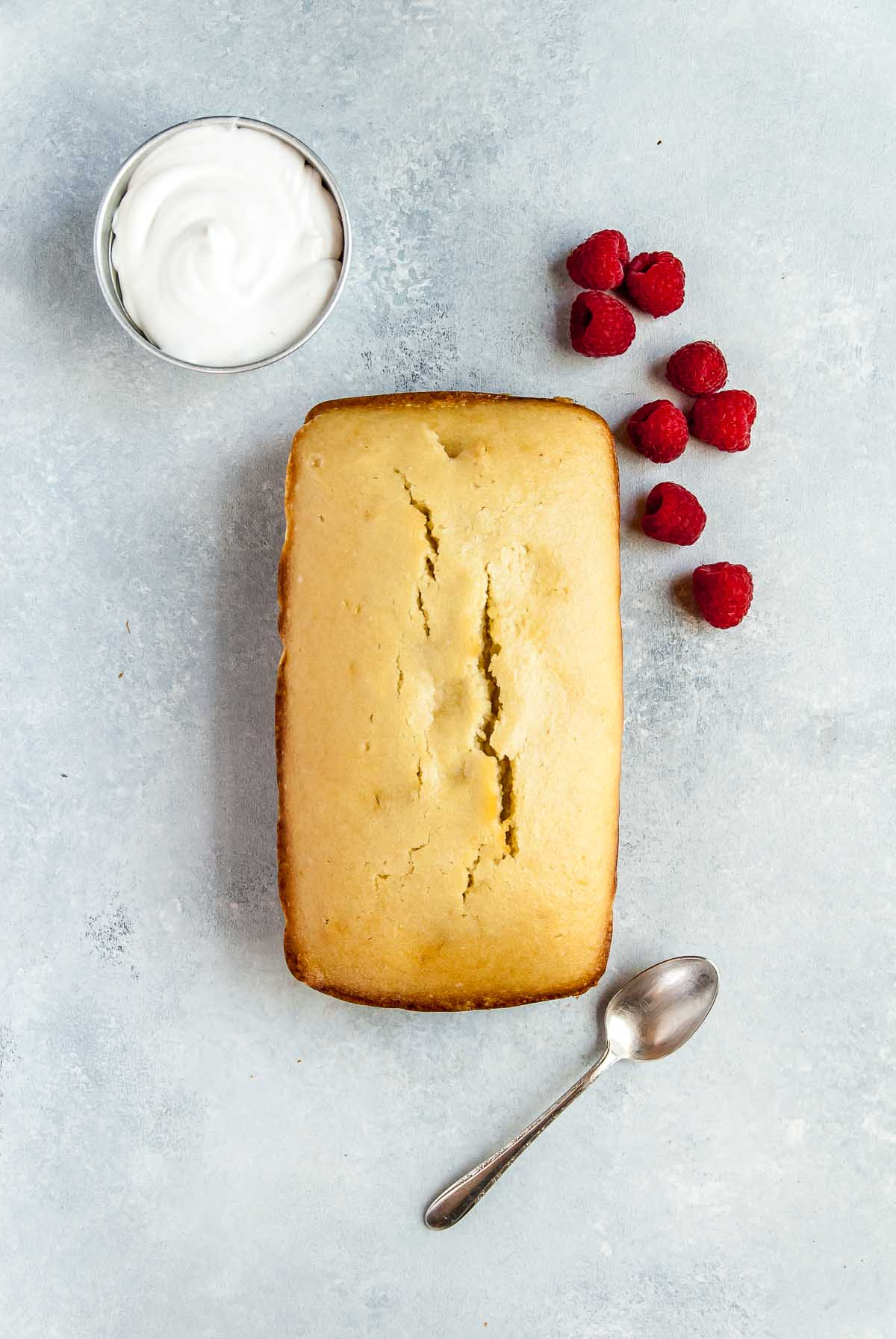 loaf of vegan pound cake with raspberries and coconut whipped cream