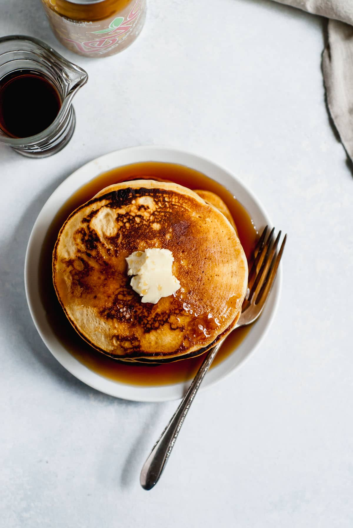 pancakes on a plate from overhead with cup of syrup and fork