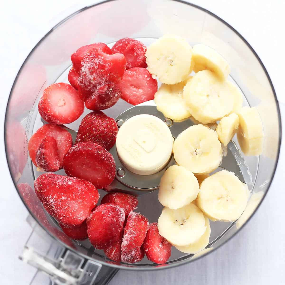 Frozen strawberries and banana slices in food processor