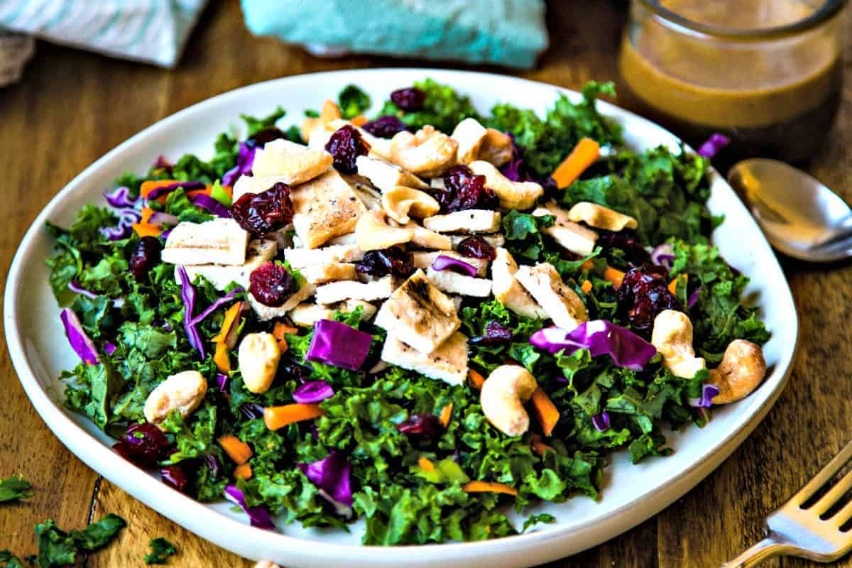 a table set with a plate of chopped chicken kale salad, a fork, scattered cashews, and a bowl of vinaigrette